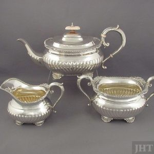 A heavy three-piece Birks sterling tea service in the Regency style, Montreal 1946-47. Fluted oblong shaped bodies with shell