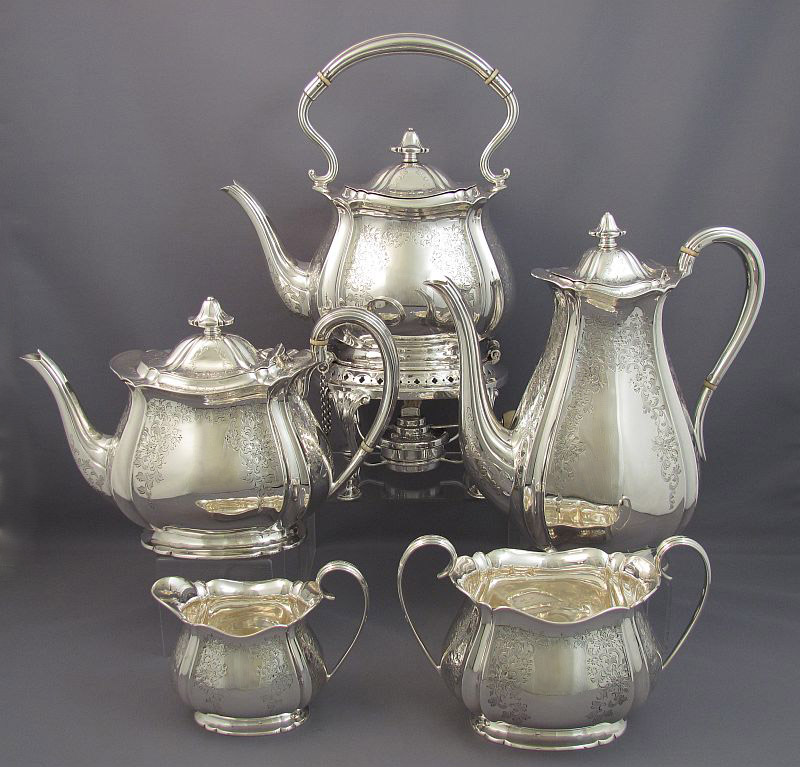 A five-piece English sterling silver tea service by Henry Atkins, hallmarked Sheffield 1924. Tapered oblong shape with scroll handles