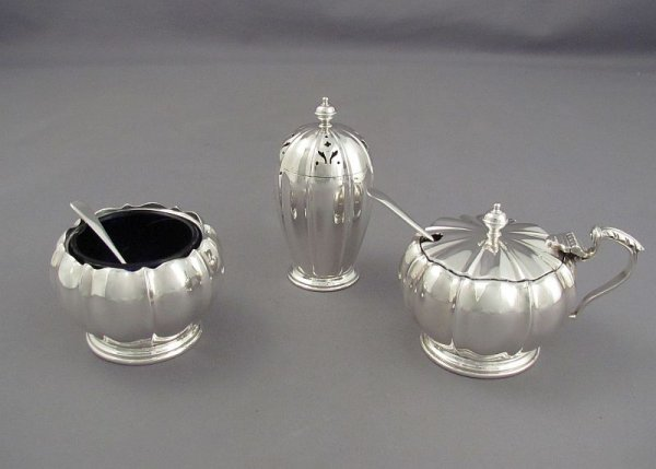 A three piece English sterling silver condiment set by Adie Brothers, hallmarked Birmingham 1954. Compressed spherical shape