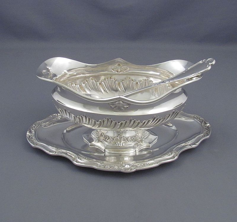 A Belgian .800 silver gravy boat and stand with matching ladle by Gustave Vanham, Brussels c. 1900. Rococo style, embossed