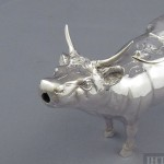 A heavy German sterling silver cow creamer, c. 1930. Realistically modeled, with a hinged lid on the back chased with a fly