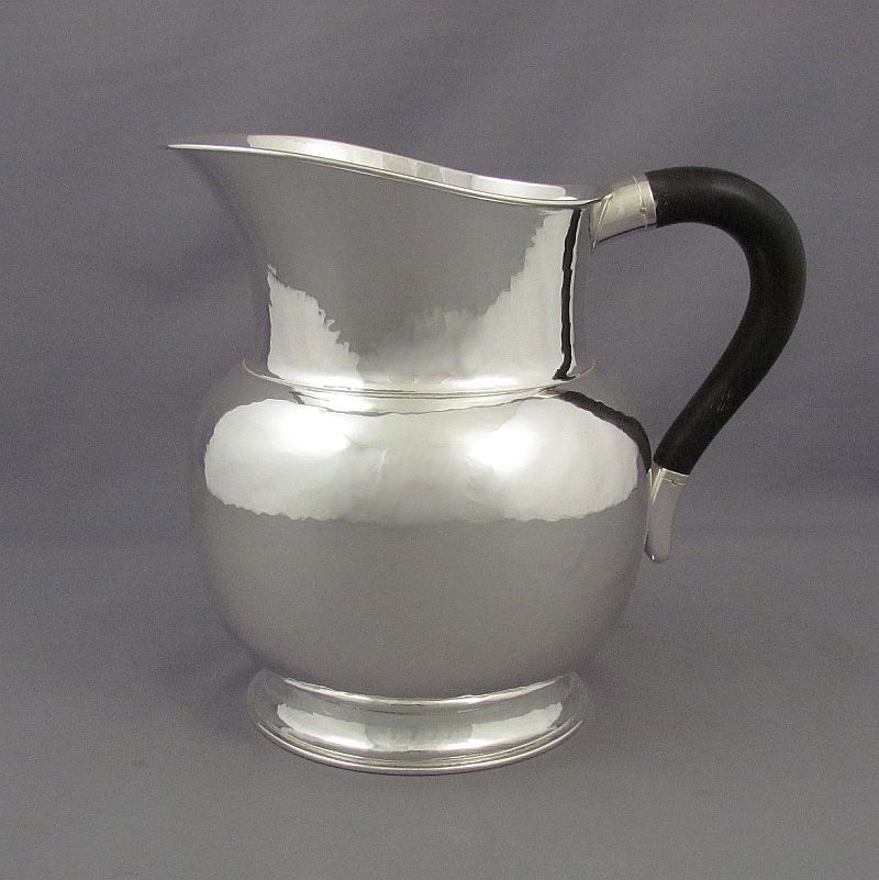 A German sterling silver water jug by MT Wetzlar, Munich c. 1936. Art Deco style with hammered finish and ebony handle