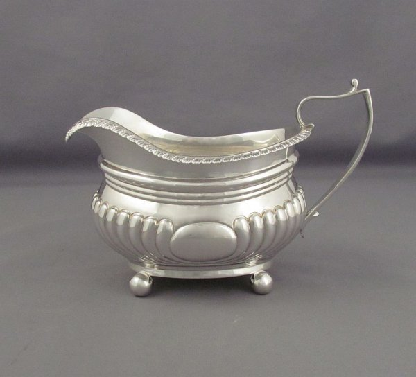 An antique George IV sterling silver cream jug by John Cope Folkard, hallmarked London 1822. Oblong, with tau shaped handle on ball