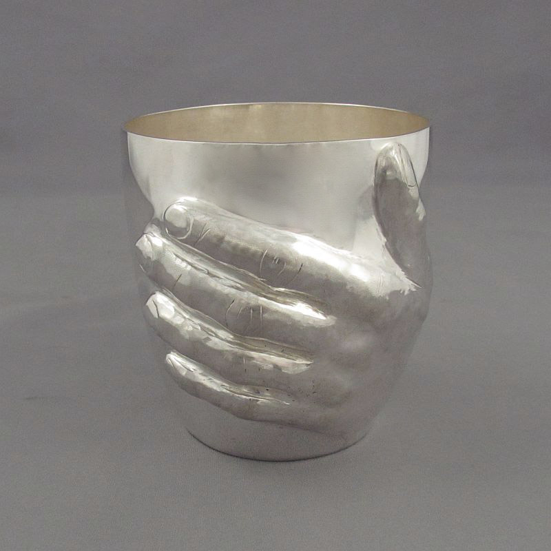 A fine quality handmade silver beaker by Canadian silversmith Ross Morrow, embossed in high relief with a man's hand