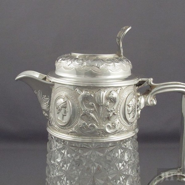 A Victorian silver claret jug by Walter & Charles Sissons, Sheffield 1895. Silver mount embossed with medallions, scrolls