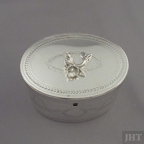 A George III silver tea caddy by Aaron Lestourgeon, hallmarked London 1774. Drum oval shape with flat lid and engraved