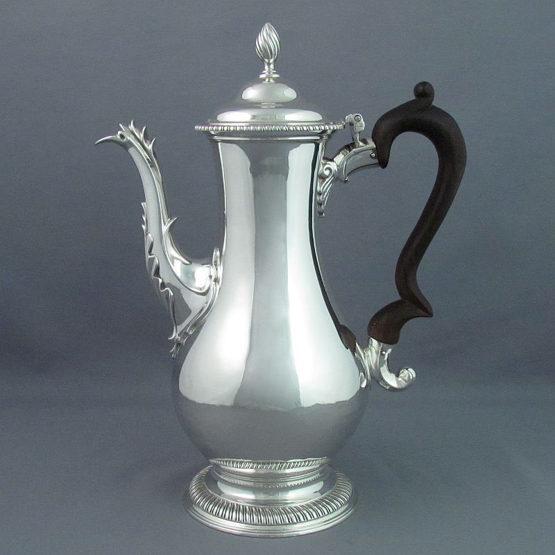 A George III silver coffee pot by Charles Wright, hallmarked London 1774. Baluster shaped with scroll spout and double scroll
