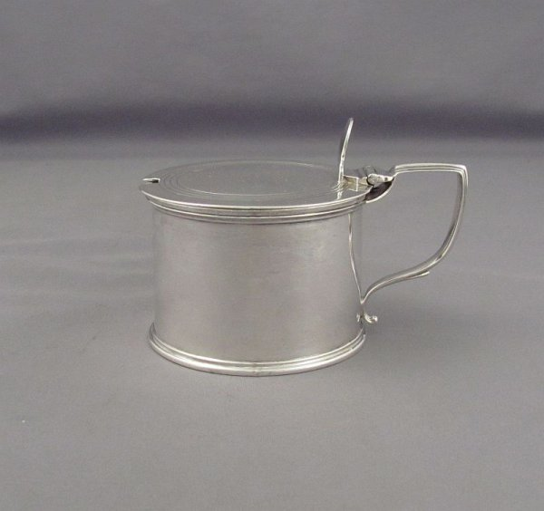 A large English Victorian sterling silver mustard pot by Henry Holland, hallmarked London 1876. Drum shaped with thread band on the