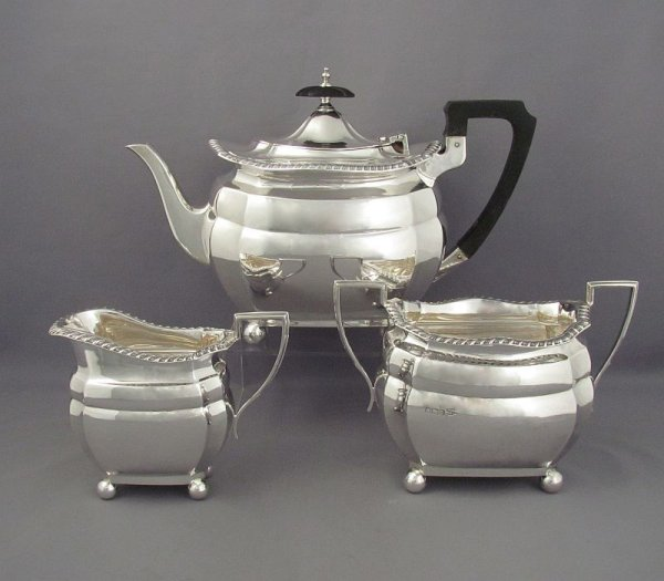 An antique Edwardian sterling silver tea set by Walker & Hall, hallmarked Sheffield 1910. Oblong shape with gadroon borders on