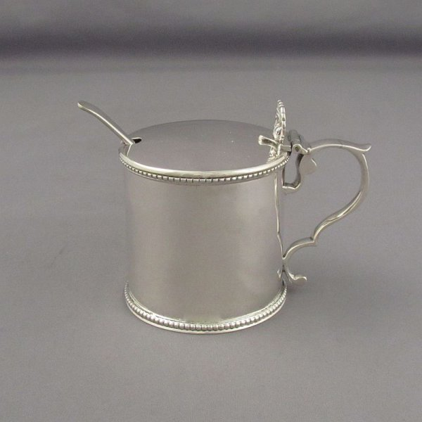 An antique Victorian sterling silver mustard pot by Henry Holland, hallmarked London 1859. Drum shaped with bead border
