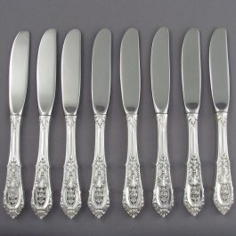A set of eight sterling butter spreaders in Rosepoint pattern by Wallace Silversmiths.
