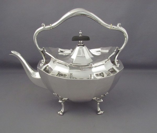An antique Scottish sterling silver kettle on stand by Wilson& Sharp, hallmarked for Edinburgh 1914. Paneled oval body with scroll