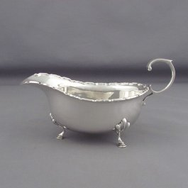An English sterling silver sauce boat by Adie Brothers, hallmarked Birmingham 1931.  Traditional boat shape with applied scroll border